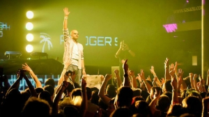 DJ Roger Shah standing in front of a nightclub crowd